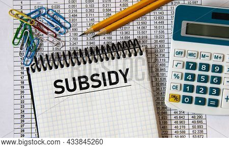 Subsidy - Word In A Notebook On The Background Of A Table With Numbers, Calculator And Pencils. Busi