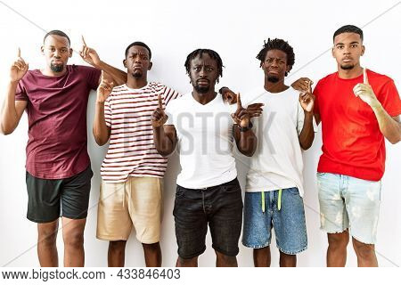 Young african group of friends standing together over isolated background pointing up looking sad and upset, indicating direction with fingers, unhappy and depressed.
