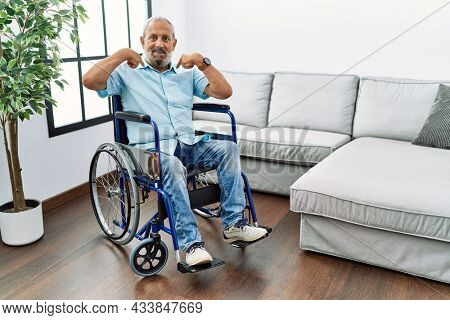 Handsome senior man sitting on wheelchair at the living room looking confident with smile on face, pointing oneself with fingers proud and happy.