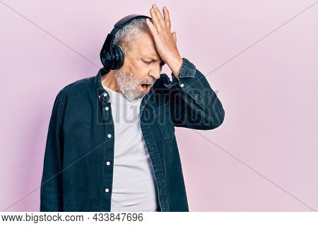 Handsome senior man with beard listening to music using headphones surprised with hand on head for mistake, remember error. forgot, bad memory concept.