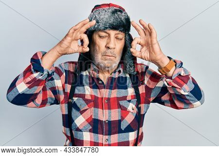 Handsome mature man wearing winter hat with ear flaps relax and smiling with eyes closed doing meditation gesture with fingers. yoga concept.