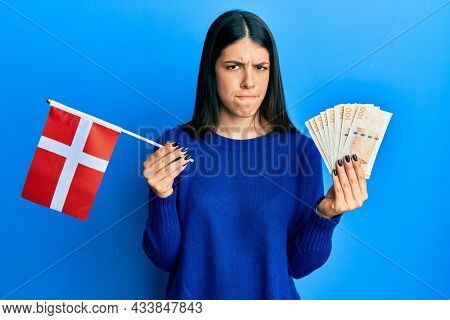Young hispanic woman holding denmark flag and krone banknotes skeptic and nervous, frowning upset because of problem. negative person.
