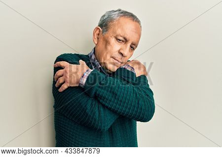 Handsome senior man with grey hair wearing casual sweater hugging oneself happy and positive, smiling confident. self love and self care