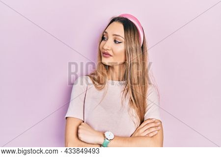 Young blonde girl wearing casual clothes looking to the side with arms crossed convinced and confident