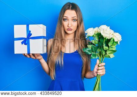 Young blonde girl holding anniversary present and bouquet of flowers skeptic and nervous, frowning upset because of problem. negative person.