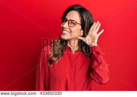 Young latin woman wearing casual clothes and glasses smiling with hand over ear listening an hearing to rumor or gossip. deafness concept.