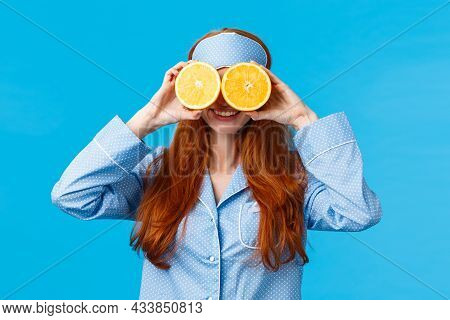 Carefree Pretty And Cute Redhead Woman In Nightwear, Sleep Mask, Holding Two Slices Of Orange Over E