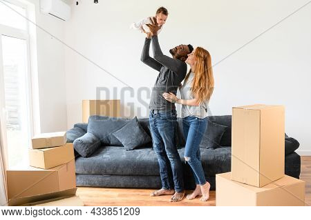 Happy Mixed-race Family Relocated In New House, African-american Husband And Caucasian Wife Standing