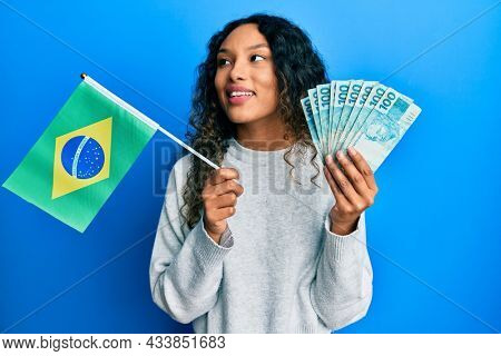 Young latin woman holding brazil flag and real banknotes smiling looking to the side and staring away thinking.