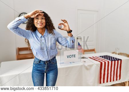 Beautiful hispanic woman standing by at political campaign by voting ballot very happy and smiling looking far away with hand over head. searching concept.