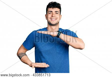 Young hispanic man wearing casual t shirt gesturing with hands showing big and large size sign, measure symbol. smiling looking at the camera. measuring concept.