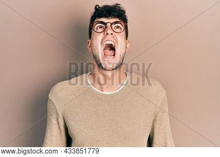 Young hispanic man wearing casual clothes and glasses angry and mad screaming frustrated and furious, shouting with anger. rage and aggressive concept.