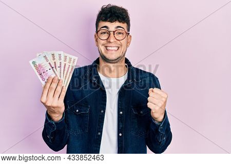 Young hispanic man holding saudi arabia riyal banknotes screaming proud, celebrating victory and success very excited with raised arm