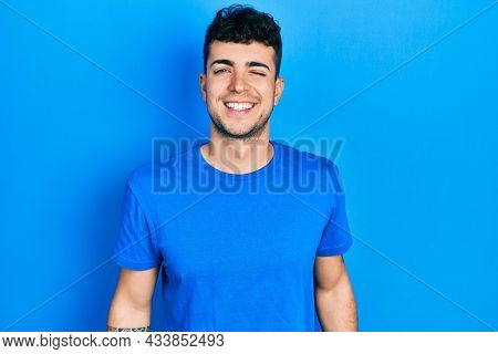 Young hispanic man wearing casual blue t shirt winking looking at the camera with sexy expression, cheerful and happy face.