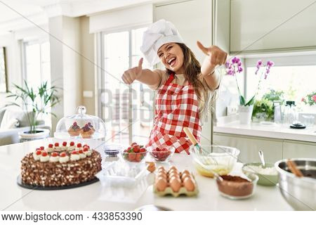 Beautiful young brunette pastry chef woman cooking pastries at the kitchen approving doing positive gesture with hand, thumbs up smiling and happy for success. winner gesture.