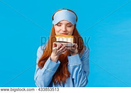 Food, Eating And Desserts Concept. Cheerful Pretty Redhead Woman In Nightwear, Sleep Mask, Close Eye