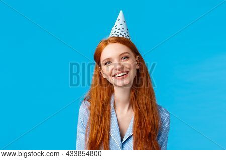 Happiness, Beauty And Celebration Concept. Cheerful Carefree Redhead Woman In B-day Hat And Nightwea