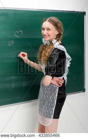 Happy School Girl In Uniform Writing At Blackboard. Beautiful Student Wearing Retro Soviet School Un