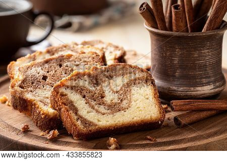Closeup Of Sliced Cinnamon Swirl Loaf Cake And Cinnamon Sticks On A Wooden Platter