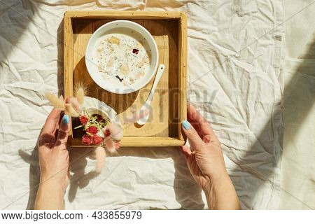 Breakfast In Bed, Female Hands Put Try With Bowl Muesli And Flower In Sunlight At Home