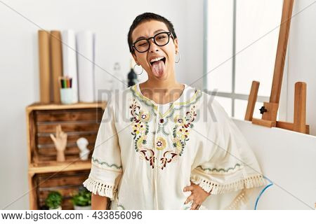 Young hispanic woman with short hair at art studio sticking tongue out happy with funny expression. emotion concept.