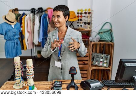 Young hispanic woman with short hair working as manager at retail boutique disgusted expression, displeased and fearful doing disgust face because aversion reaction. with hands raised
