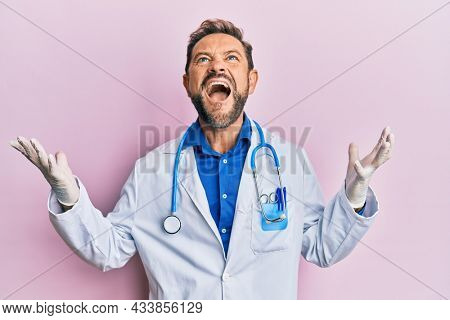 Middle age man wearing doctor uniform and stethoscope crazy and mad shouting and yelling with aggressive expression and arms raised. frustration concept.
