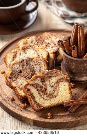 Sliced Cinnamon Swirl Loaf Cake And Cinnamon Sticks On A Wooden Platter