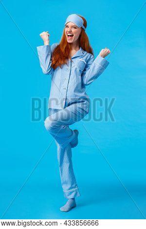 Win, Luck And Happiness Concept. Cheerful Caucasian Redhead Female In Nightwear And Sleep Mask Feeli