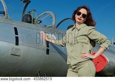Military and commercial aircraft. Portrait of a confident pilot woman wearing uniform and sunglasses posing next to her fighter jet.