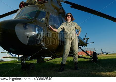 Full length portrait of a professional female commercial aviation pilot woman in uniform and sunglasses poses happily smiling in the background of a helicopter on the airfield. Aviation.