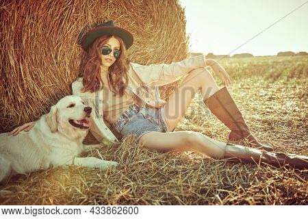 Summer and autumn fashion. Full length portrait of a romantic girl sitting in the field by a haystack with a dog beside her. Modern hippie style. Wild west style.