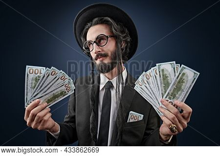 Portrait of a wealthy Jewish man with  bundles of banknotes. Rich Jew concept. Studio shot in a dark blue background.