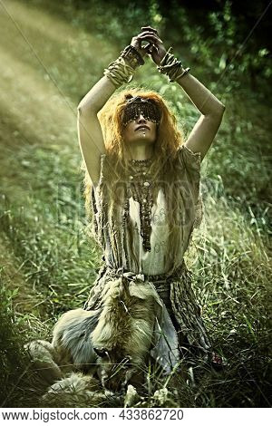 Ancient woman shaman in ritual garment and with a mask covering her eyes doing authentic ritual of summoning spirits. Paganism. Forest witch. Halloween.