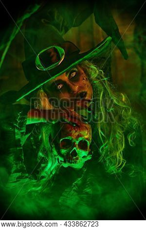 Halloween. A frightening old witch holds a skull in an old wooden house. Magical green and red light.