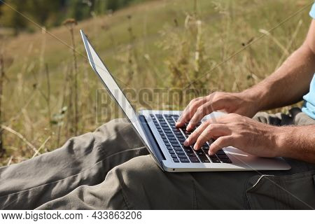 Man Working With Laptop Outdoors On Sunny Day, Closeup