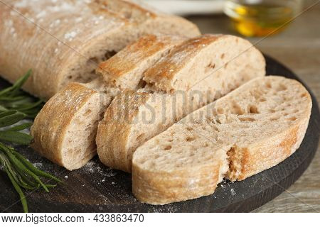 Cut Delicious Ciabatta With Rosemary On Table, Closeup