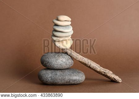 Stack Of Stones Balancing On Wooden Stick Against Brown Background. Harmony Concept