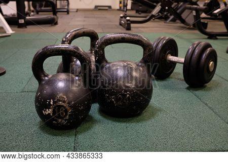 Dumbbells And Kettlebells On A Floor. Bodybuilding Equipment. Fitness Or Bodybuilding Concept Backgr
