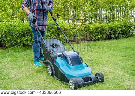 Gardener Use Lawn Mover Machine Cut Green Grass, Hobby Planting Home Garden.