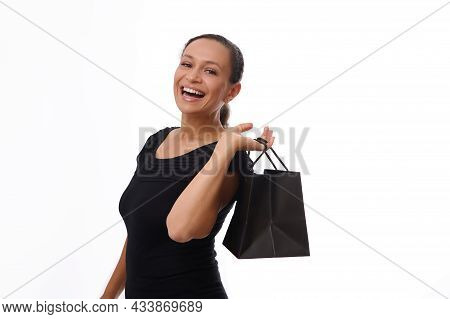 Happy Cheerful Woman Dressed In Black Attire Holds A Black Shopping Bag And Laughs, Smiles With Beau
