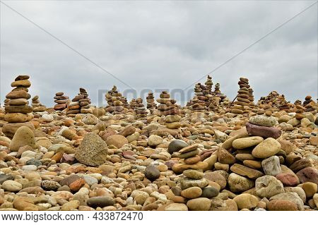 A View Of Stone Cairns Made From Beach Pebbles On The Northumberland Island Of Lindisfarne In Englan