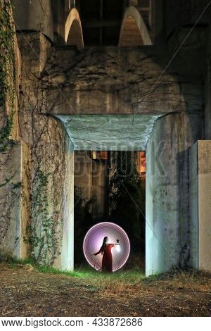 Pretty Girl Holding a Lantern in a Concrete Doorway