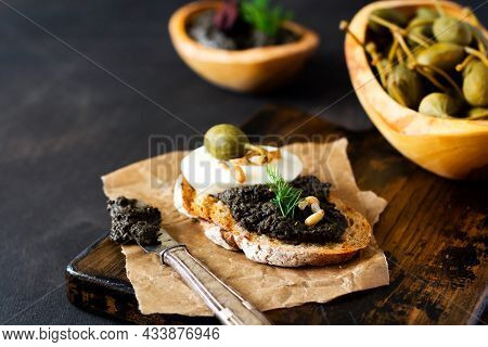 Sandwich With Slice Of Mozzarella Cheese And Tapenade, Caper On Dark Rustic Table Background. Tradit