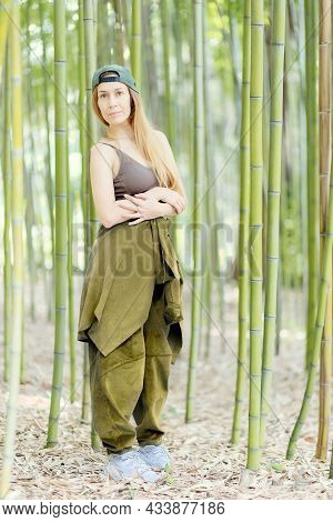 Hip-hop Girl Stands With Folded Arms In A Green Bamboo Grove