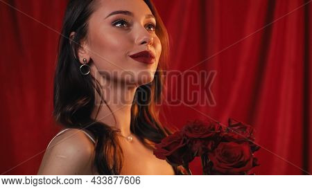 Pleased Young Woman With Bright Lips Holding Roses On Red.