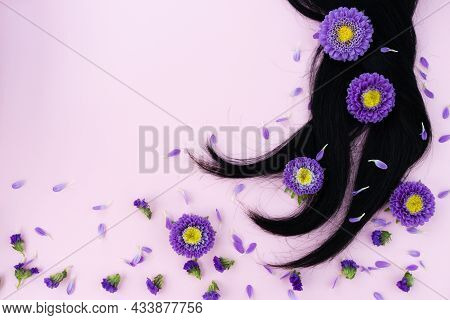 Black Hair With Lilac Flowers And Petals On It. Hair Care Concept.