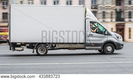 Ford Transit Speeding On Road. Gray Ford Transit Cargo Box Van In Motion. Moscow, Russia - July 2021