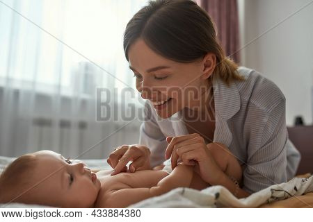 Cheerful Mother Playing With Adorable Baby, Stimulating Its Development By Providing Skin Contact. Y