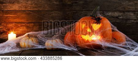 Halloween, decorations and holidays concept - pumpkins with spiders, web and candles